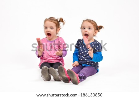 Twin girls eating ice cream and enjoying each other's company - stock photo