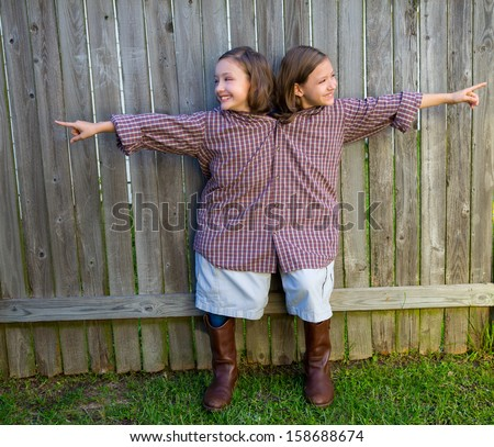 twin girls fancy dressed up pretending be siamese with his father shirt pointing finger - stock photo