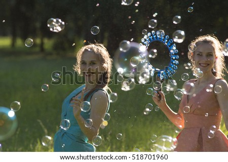 Twin girls make big soap bubbles in the park