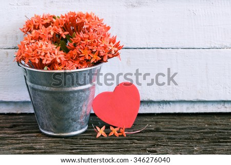 Twin hearts and flowers in zinc bucket on wooden table.Valentine vintage and retro background. - stock photo