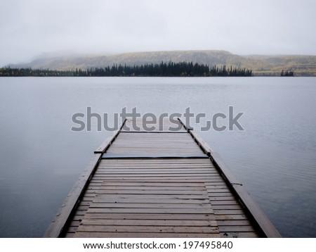 Twin Lakes, Yukon Territory, Canada, wooden floating boat dock on gray rainy day in autumn fall - stock photo