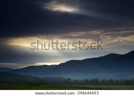 Twin light shafts breaking through at dawn in Cades Cove