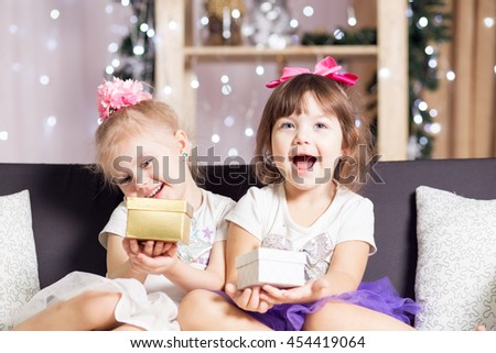 twin little girls in skirts tutu near a Christmas tree sitting on the couch opened new year gifts and rejoice - stock photo