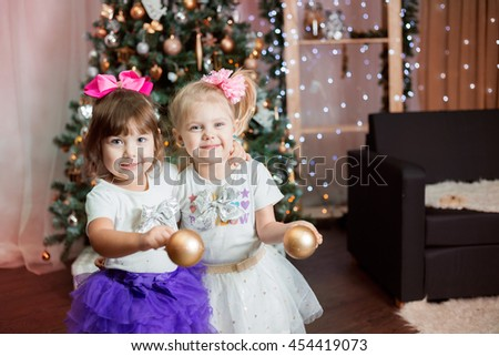 twin little girls in skirts tutu near a Christmas tree with Christmas balls cheerful smile