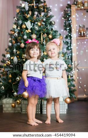twin little girls in skirts tutu near a Christmas tree with new year balls fun - stock photo