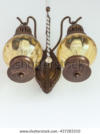Twin metal lantern on the white wall of old house. - stock photo