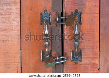 twin padlock on a wooden door. - stock photo