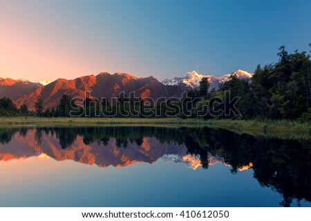 Twin Peaks reflect in the beautiful Lake Matheson at sunset, Southern Alps, South Island, New Zealand - stock photo