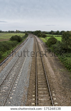 Twin railway tracks curving to the left, UK standard gauge