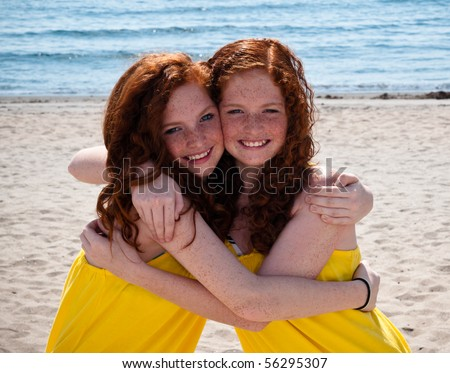 Twin Red-Headed teenage girls playing at the beach - stock photo