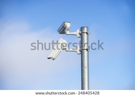 Twin security cameras on a pole against a blue sky and hazy cloud - stock photo