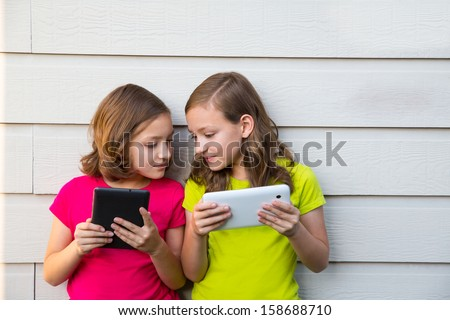 Twin sister girls playing with tablet pc happy on white wall looking each other - stock photo