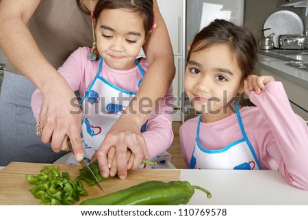 Twin sisters and mother chopping vegetables together on the kitchen counter at home. - stock photo