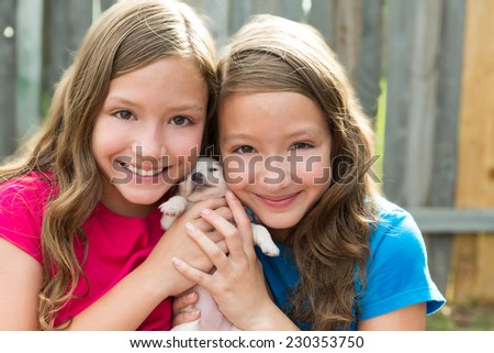 Twin sisters and puppy pet dog chihuahua playing together with doggy - stock photo