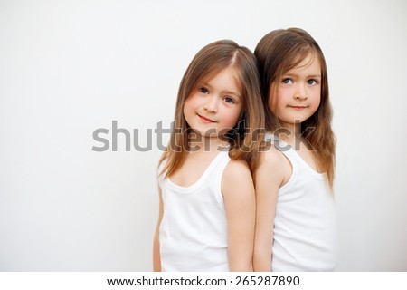 Twin sisters are happy on a white background - stock photo