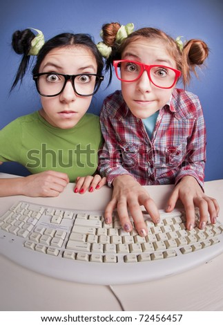 Twin sisters at the computer - stock photo