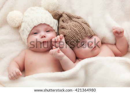 Twin sisters babies lying together wearing funny woolen bobble hats. Happy childhood - stock photo