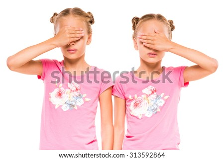 Twin sisters closed their face with hands, standing on white background. - stock photo