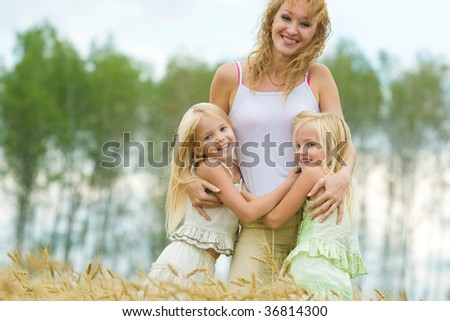 Twin sisters embracing their mother and laughing in wheat field - stock photo
