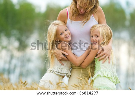 Twin sisters embracing their mother with smiles in wheat field - stock photo