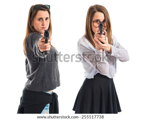 Twin sisters shooting with a pistol - stock photo
