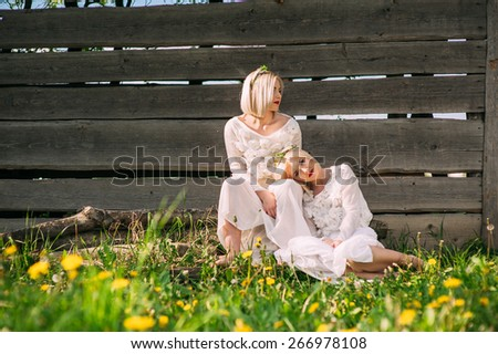 Twin sisters sitting at a wooden wall - stock photo