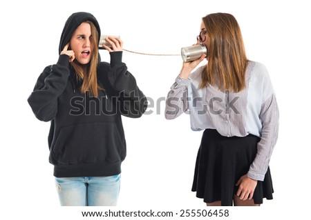 Twin sisters talking through tin phone  - stock photo