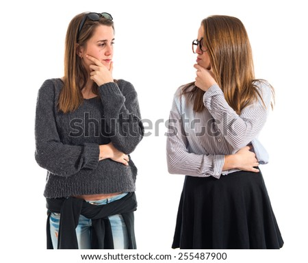 Twin sisters thinking and looking each other - stock photo