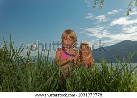 twin sisters walking around the beach  during vacation at the Lago Maggiore in Italy