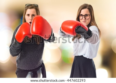 Twin sisters with boxing gloves on unfocused background