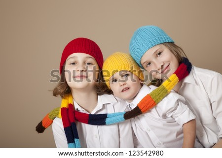 Twin sisters with little brother and caps during Christmas - stock photo