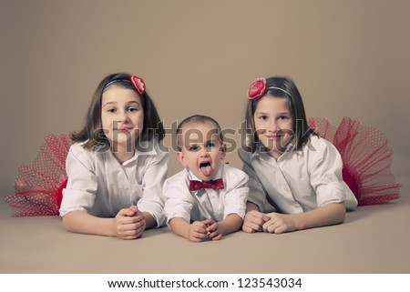 Twin sisters  with little brother during Christmas - stock photo