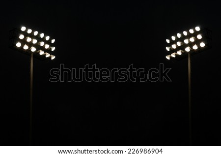 Twin Stadium Lights At A Sports Stadium At Night With Copy Space - stock photo