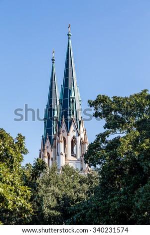 Twin Steeples of Savannah Church Over Trees - stock photo