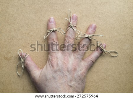 Twine in the fingers of an elder. Wooden background - stock photo