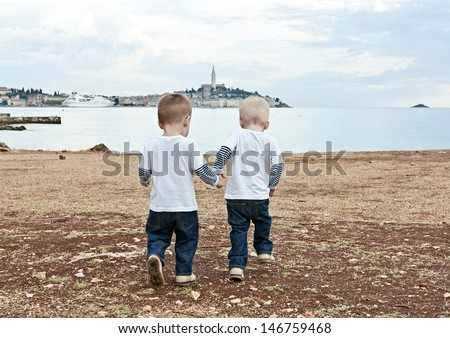 Twins go by a hand on a beach in the evening. Rovinj. Croatia. - stock photo