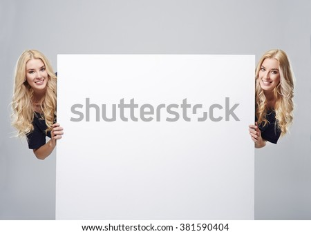 Twins on the both sides of empty placard - stock photo