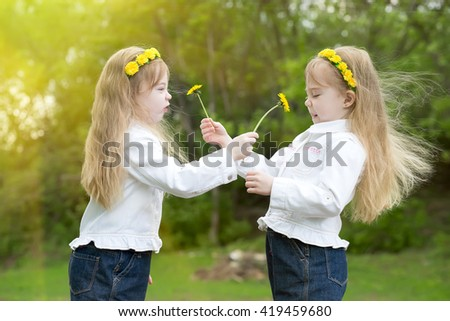 twins play with dandelions on a glade in park - stock photo