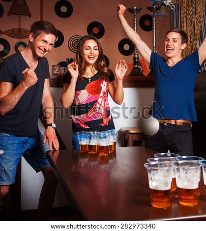 Twins playing beerpong with beautiful brunette in bar. square photo - stock photo