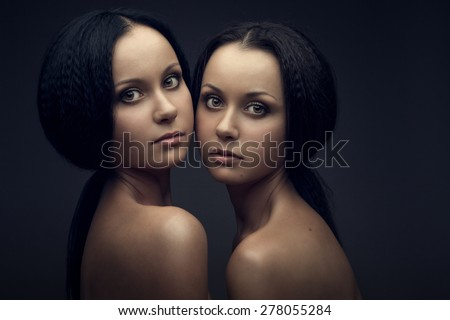 Twins portrait isolated on black background - stock photo