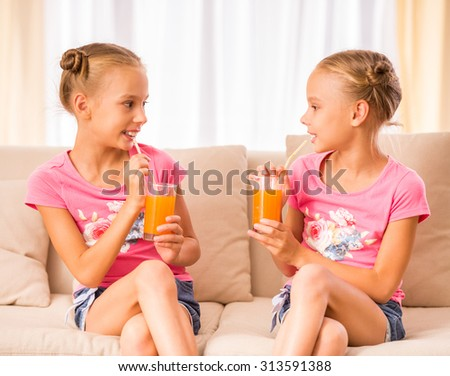 Twins sisters are drinking juice and talking while sitting on the couch at home. - stock photo