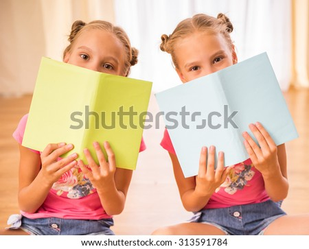 Twins sisters are having fun while reading a books sitting on the floor. - stock photo