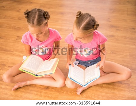 Twins sisters are reading a books sitting on the floor. - stock photo