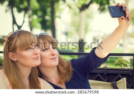 Twins sisters taking selfie with mobile phone in a restaurant. Young pretty girls have fun at summer day. Warm color toned image. - stock photo