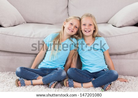 Twins sitting on a carpet in the living room - stock photo