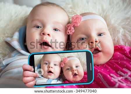 Twins taking selfie with a cell phone camera - stock photo