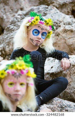 Twins with black clothing and sugar skull makeup outdoors - stock photo