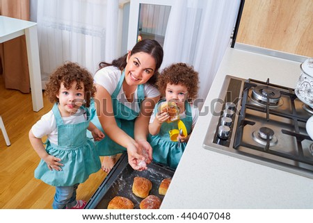 Twins with her mother in the kitchen together preparing meals. Mom with a tray of buns uybaetsya teaches kids to cook twins. Happy family with twins. The concept of a happy family. - stock photo