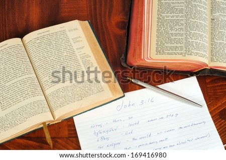 TWINSBURG, OH - JANUARY 16, 2011: Photo of two open Bibles, one Greek, the other  English, with study notes, illustrating the concept of researching the original language in Christian Bible study. - stock photo
