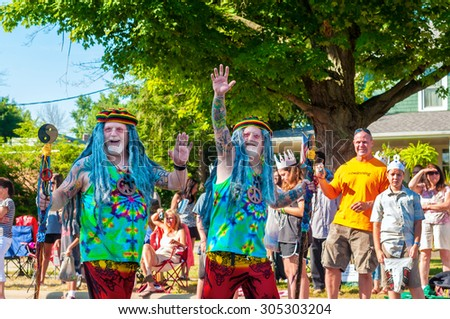 TWINSBURG, OH, USA - AUGUST 8, 2015: Twin brothers dressed as aging hippies wave in the Double Take Parade, part of the 40th annual Twins Day festival, the largest gathering of twins in the world. - stock photo
